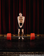 Funny picture of a wimpy skinny weight lifting competitor on stage in front of a set of barbells. The little man is standing with his knees together and hands clasped in front of him looking very timid and weak.